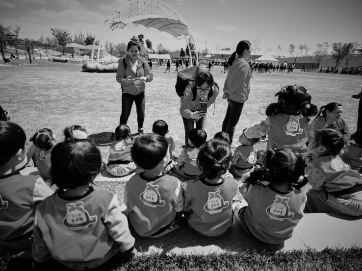 Kindergarden kids with their teachers. Waiting for the animal show to start. GFX + 23mm